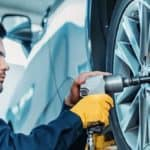 mechanic using pneumatic socket driver to remove tires