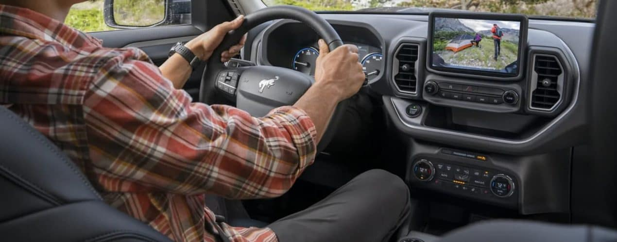 A man inside a 2021 Ford Bronco Sport is looking at the backup camera view.