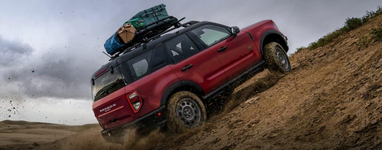 A red 2021 Ford Bronco Sport is off-roading up a muddy hill.