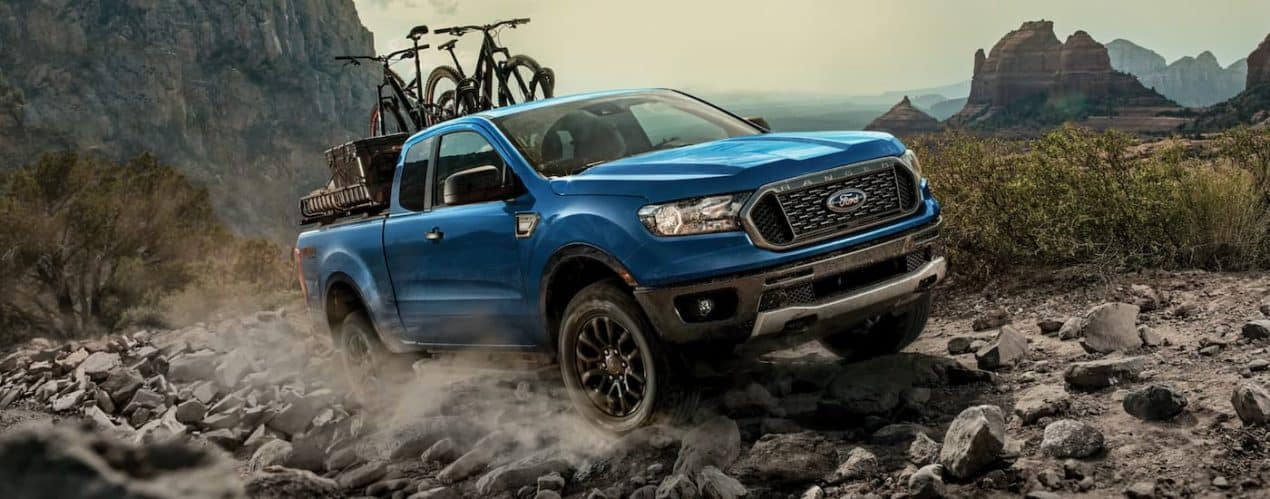 A blue 2021 Ford Ranger FX4 is off-roading with bikes on the roof.