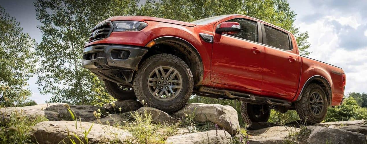 A red 2021 Ford Ranger Tremor, shown from a low angle, is off-roading on a rocky trail.