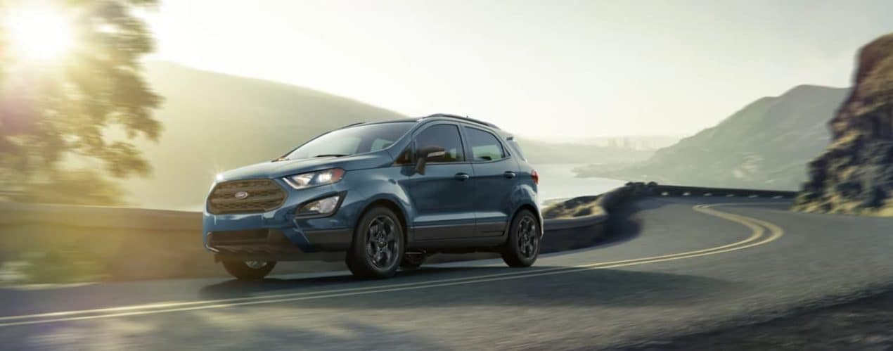 A blue 2021 Ford EcoSport is driving on a winding mountain road.