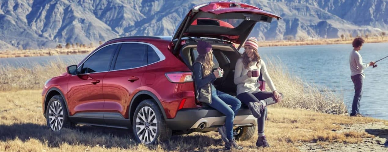 Two women are sitting in the open trunk of a red 2021 Ford Escape next to a man fishing with mountains in the distance.