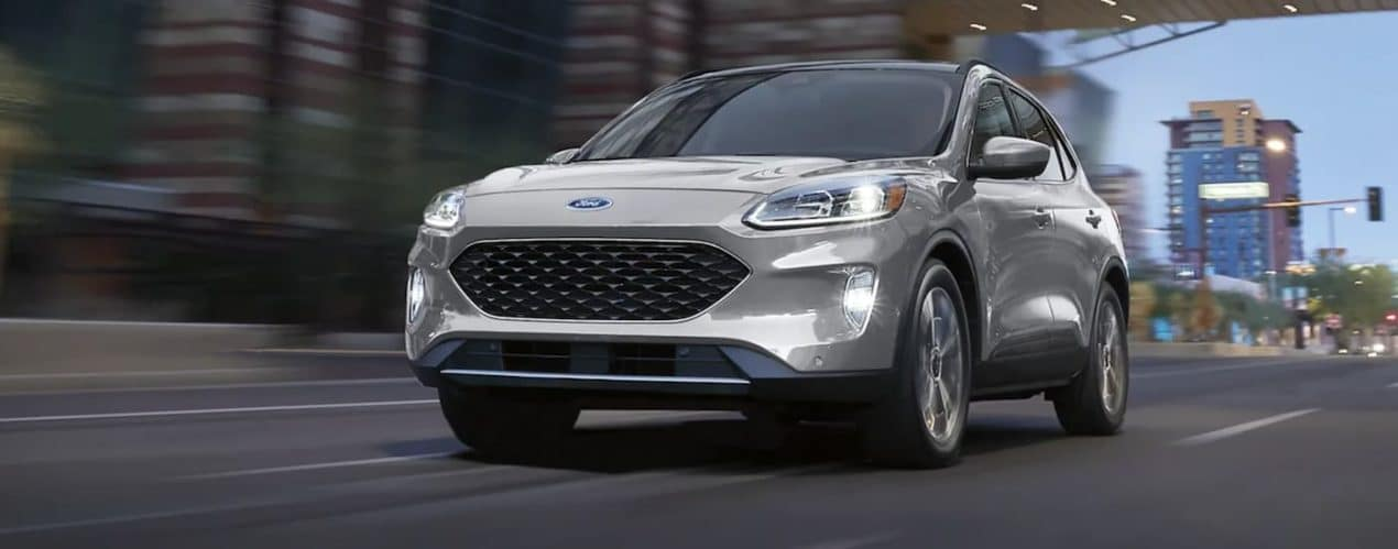 A silver 2021 Ford Escape is driving on a city street at dusk.