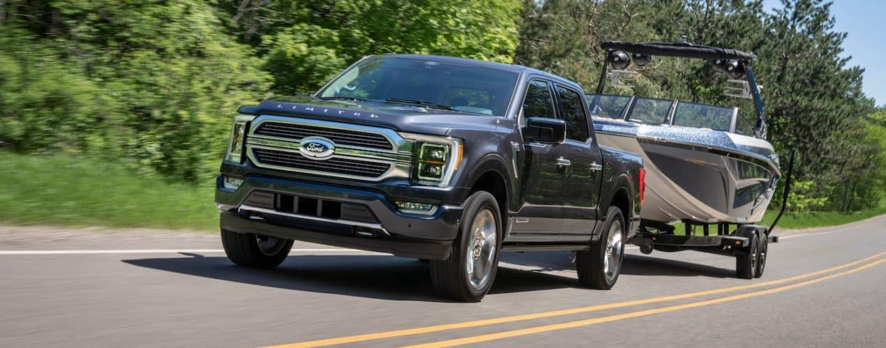 A black 2021 Ford F-150 Limited is towing a boat on a highway in front of trees.