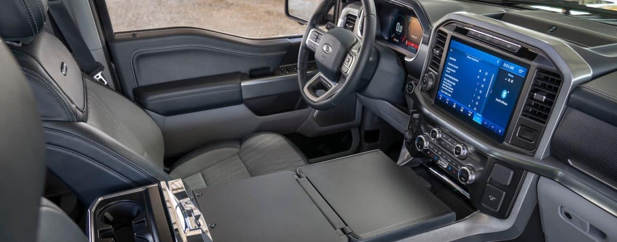 The gray interior and center console of a 2021 Ford F-150 are shown next to the dashboard and infotainment screen.