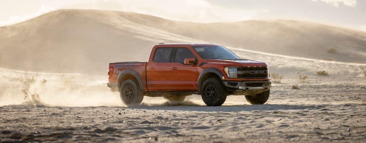 A red 2021 Ford F-150 Raptor is kicking up sand in a desert.
