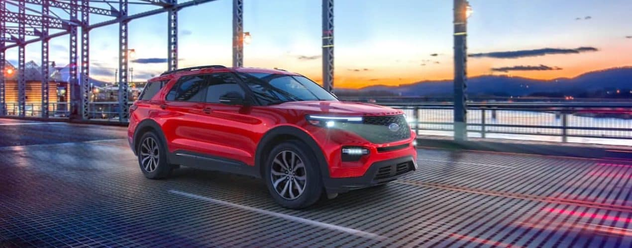 A red 2021 Ford Explorer is shown from the side driving over a bridge.