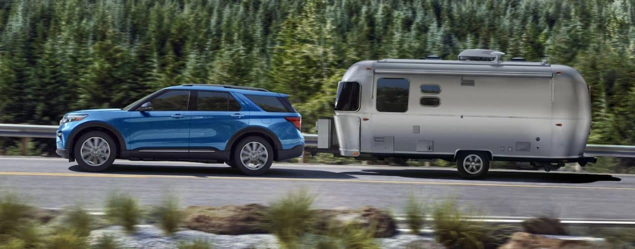 A blue 2021 Ford Explorer is towing an Airstream past pine trees.
