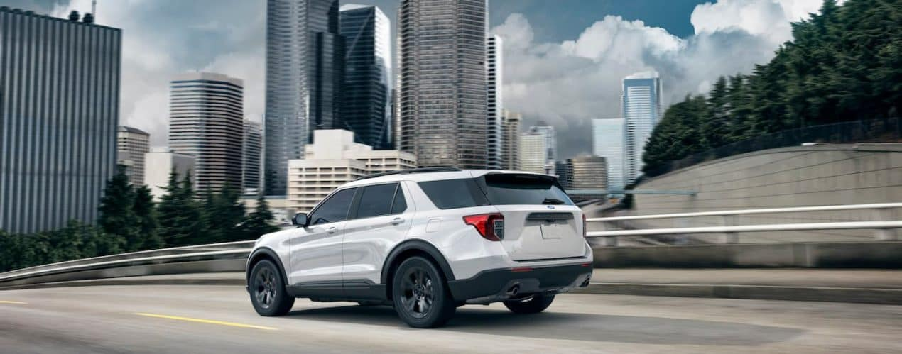 A white 2021 Ford Explorer is driving on a highway past a city.