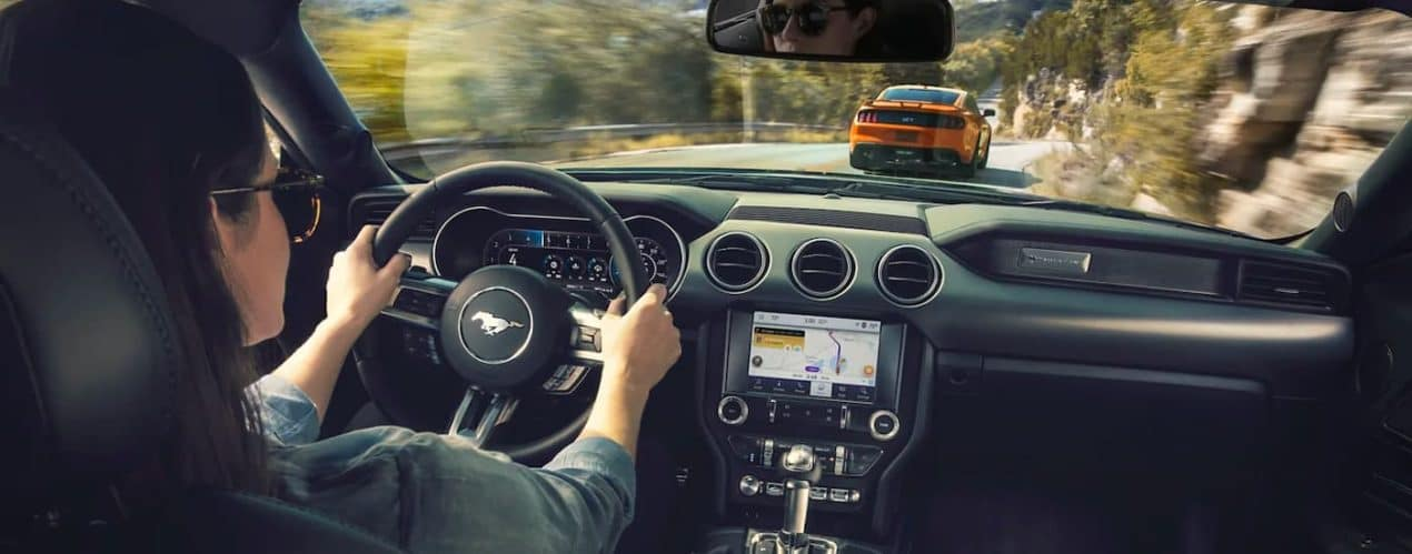 The interior of a 2021 Ford Mustang is shown with a female driver.