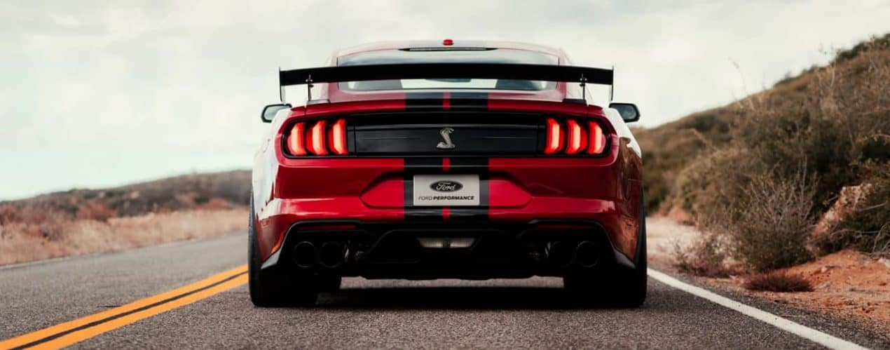 A red 2021 Ford Mustang GT500 is shown from the rear on a rural road.