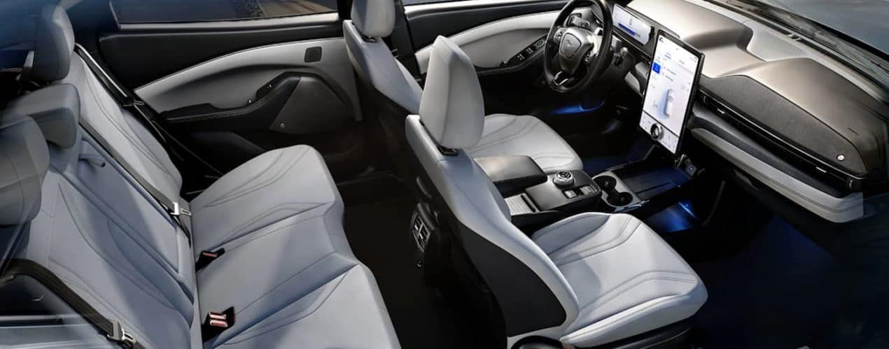 The white and black interior of a 2021 Ford Mustang Mach-E is shown from the side.