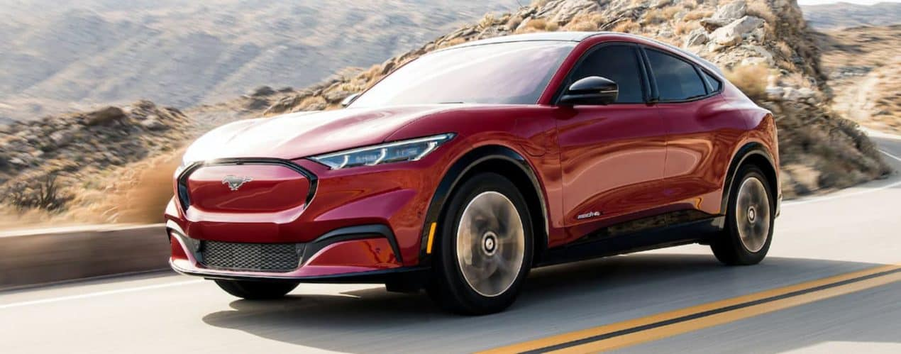 A red 2021 Ford Mustang Mach-E is driving on a desert road.