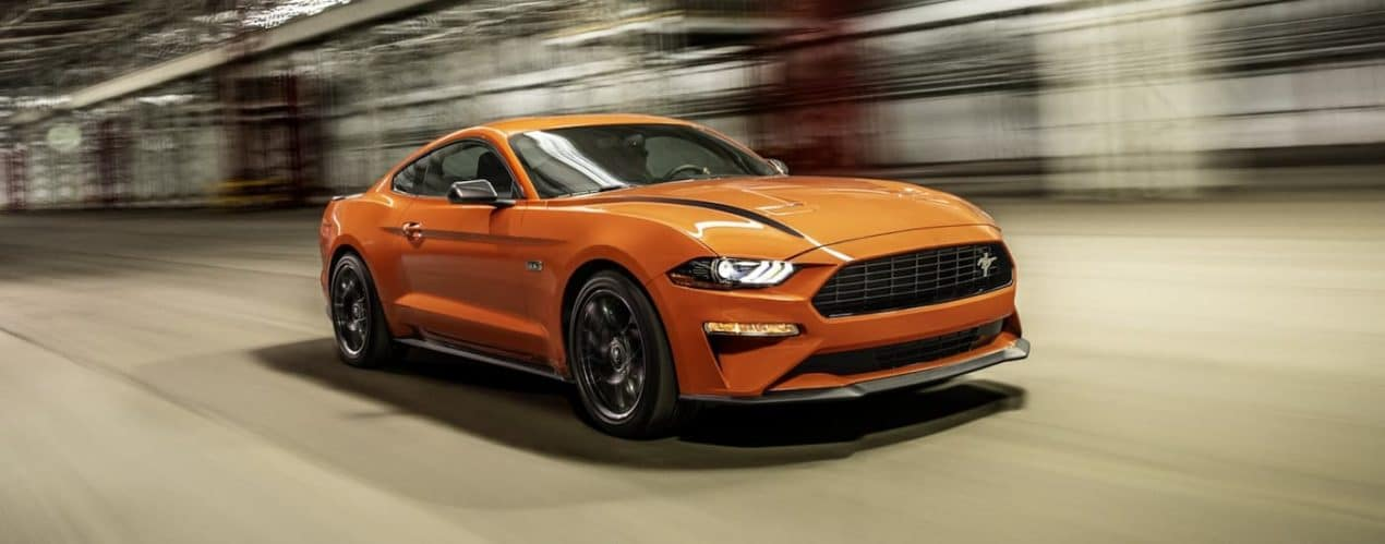 An orange 2021 Ford Mustang is driving on a city street.