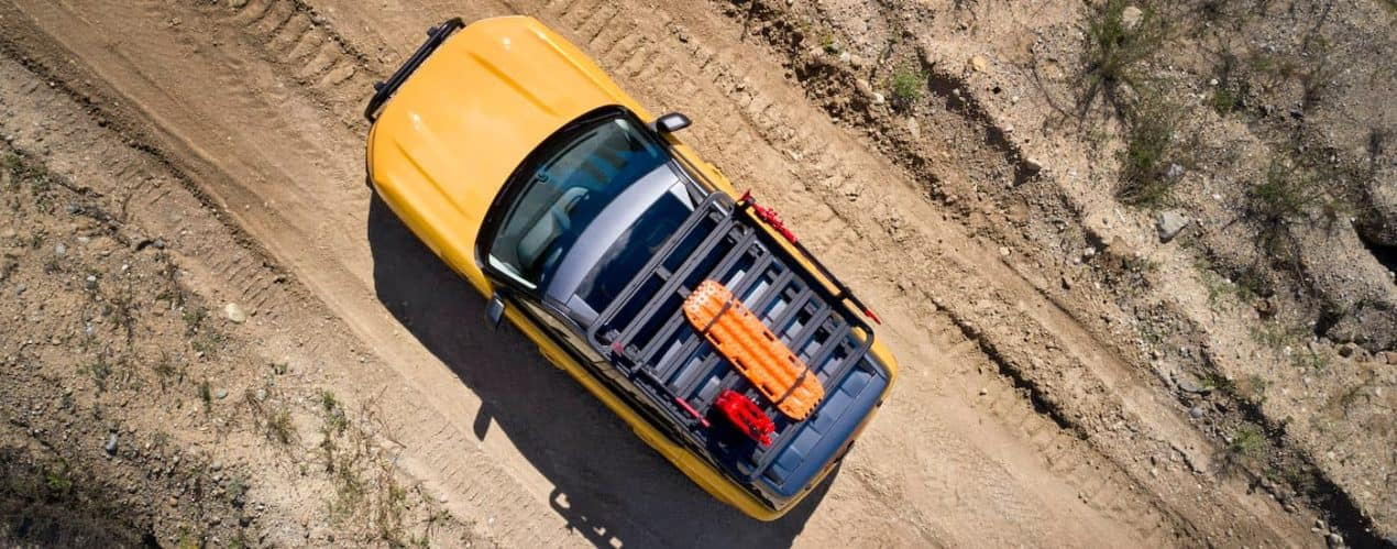 A yellow 2021 Ford Bronco Badlands 4dr is shown from a high angle towing a trailer down a dirt path.