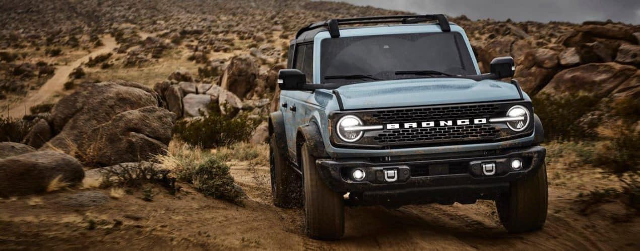 A pale blue 2021 Ford Bronco Badlands 4dr is shown from the front driving down a dirt path after winning a 2021 Ford Bronco vs 2021 Toyota 4Runner comparison.