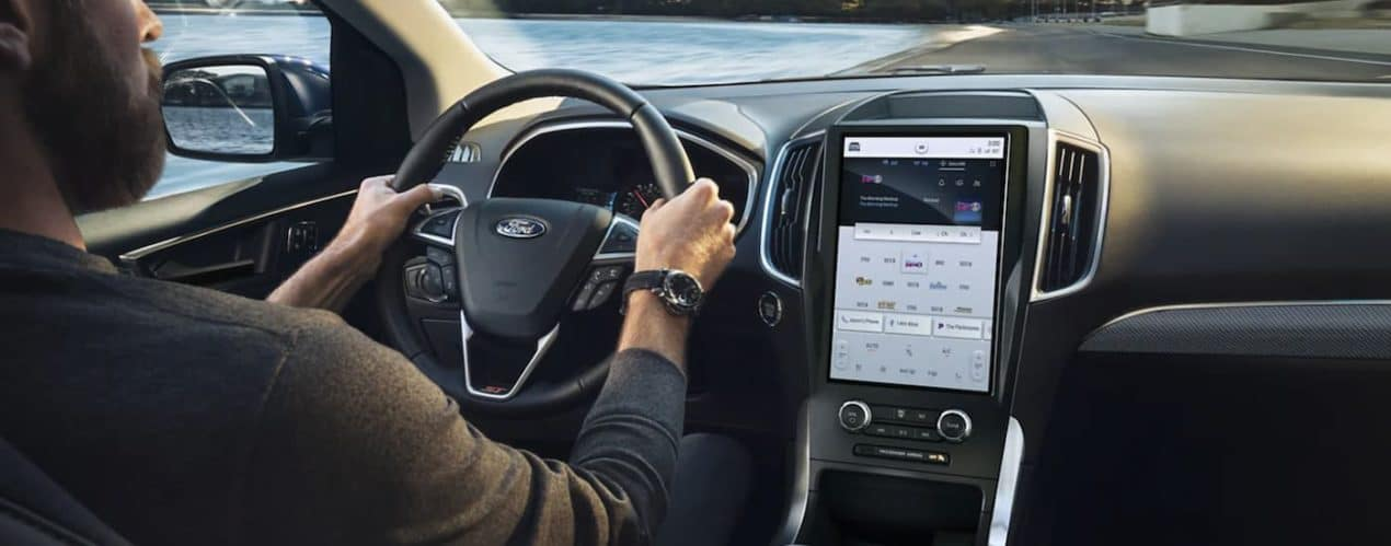 A person is shown driving a 2021 Ford Edge from an interior view.