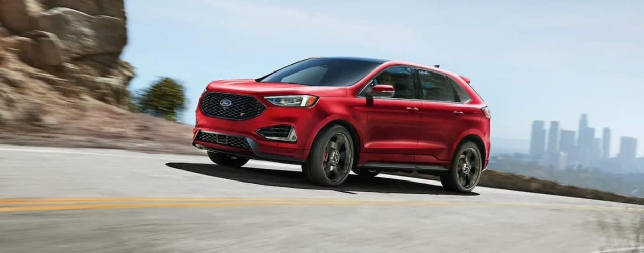 A red 2021 Ford Edge is driving around a corner with a view of a city skyline.