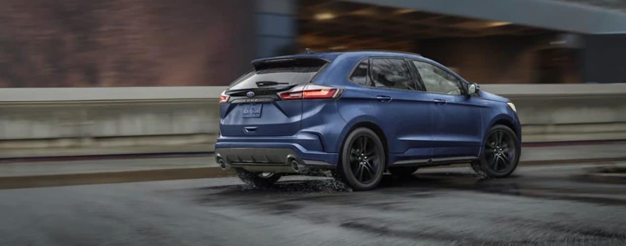 A blue 2021 Ford Edge is driving on a wet highway past an industrial site.