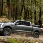 A grey 2022 Ford F-150 Lighting is shown driving through the woods after leaving a Tennessee Ford truck dealer.