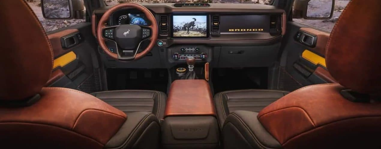 The steering wheel and dashboard of a 2021 Ford Bronco with brown and black leather seats.
