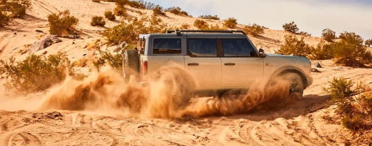 A silver 2021 Ford Bronco 4-door is shown from the side kicking up sand on a trail.