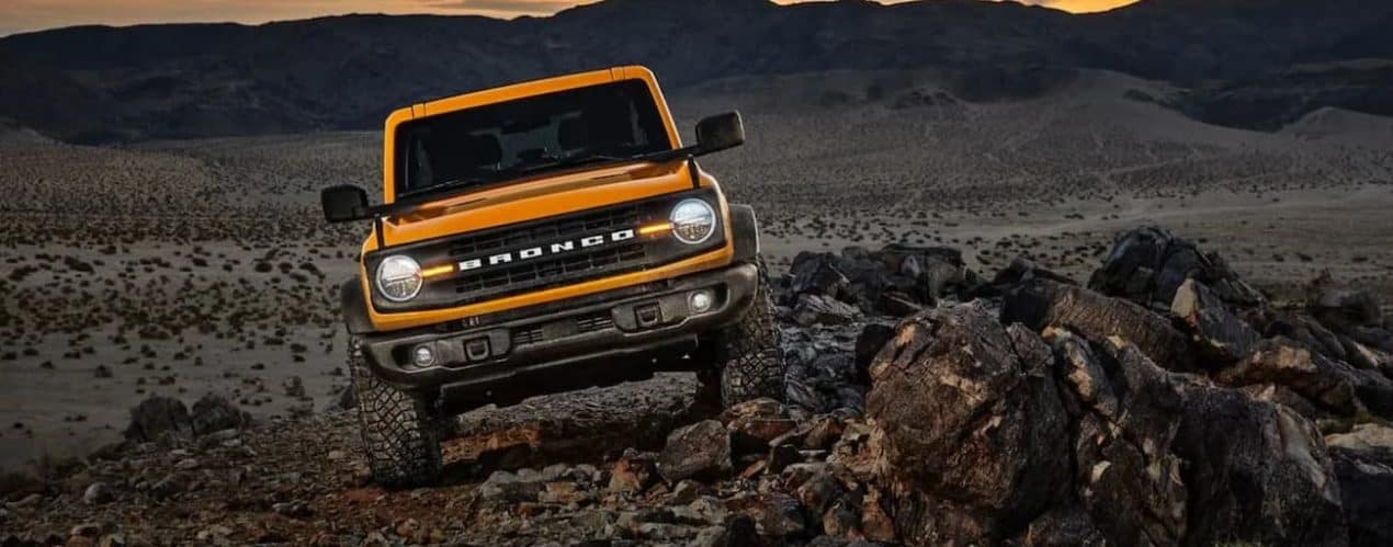 A yellow 2021 Ford Bronco is shown off-roading in a rocky desert at night.