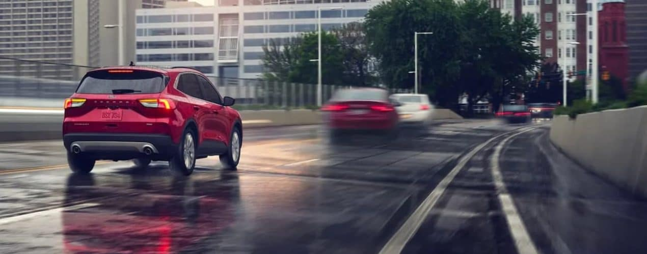 A red 2021 Ford Escape Hybrid Titanium is shown from the rear driving down a wet highway.