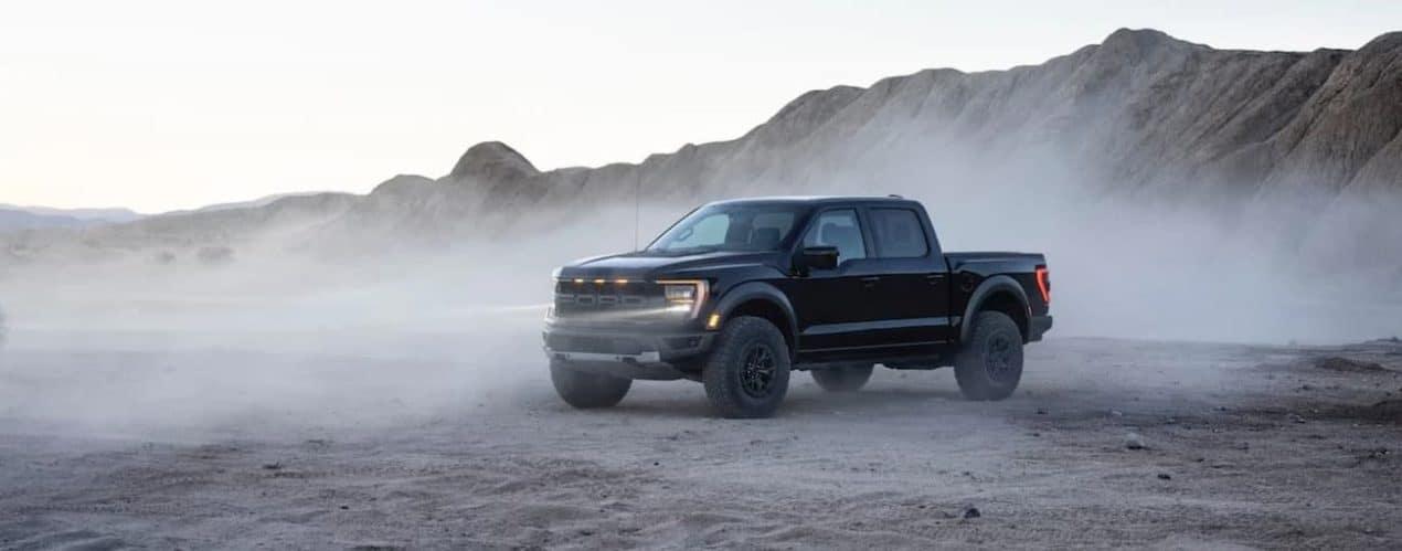 A black 2021 Ford F-150 Raptor is parked in a misty desert.