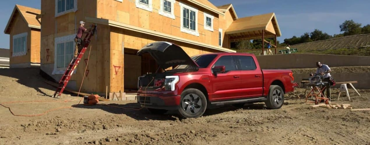 A red 2022 Ford F-150 Lightning is shown powering a compressor on a construction site.