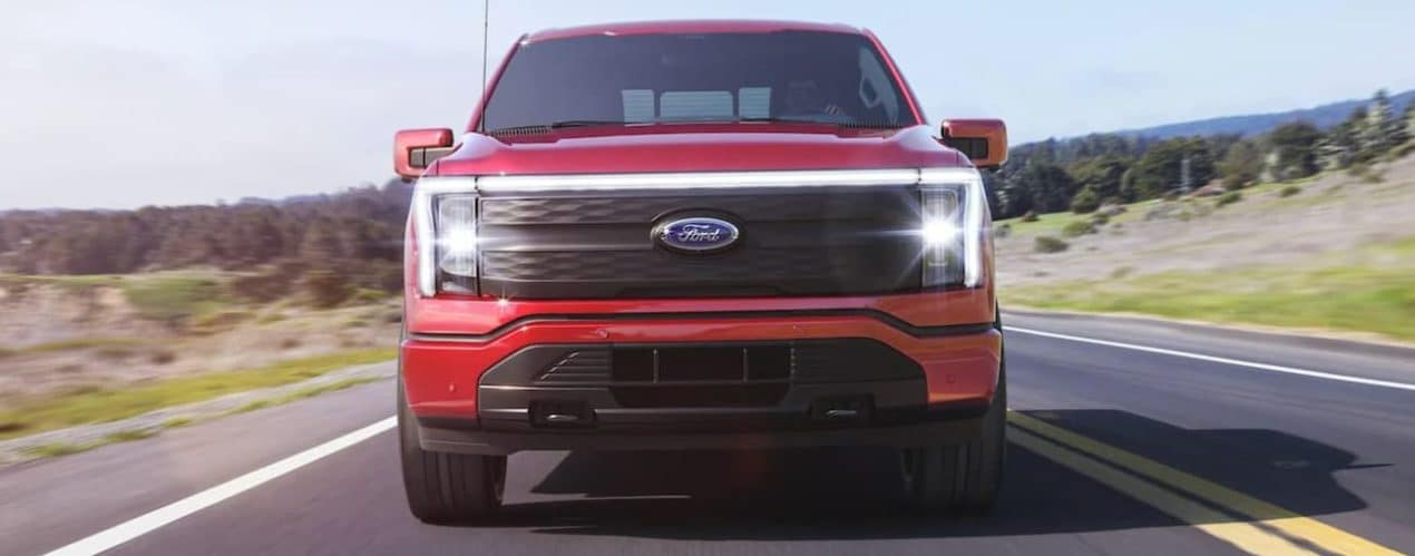 A red 2022 Ford F-150 Lightning Lariat is shown from the front driving down an empty road.