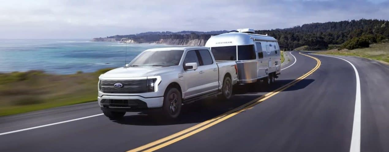 A white 2022 Ford F-150 Lightning Lariat is shown towing an Airstream past a body of water.