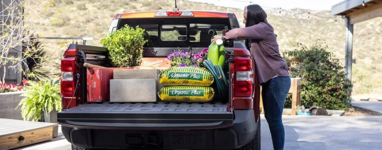 A red 2022 Ford Maverick Lariat is shown with gardening supplies in the bed.