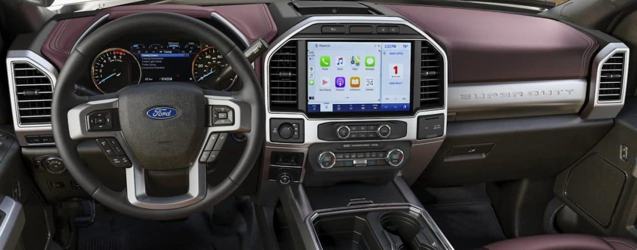 The interior of a 2022 Ford Super Duty shows the steering wheel and infotainment screen.