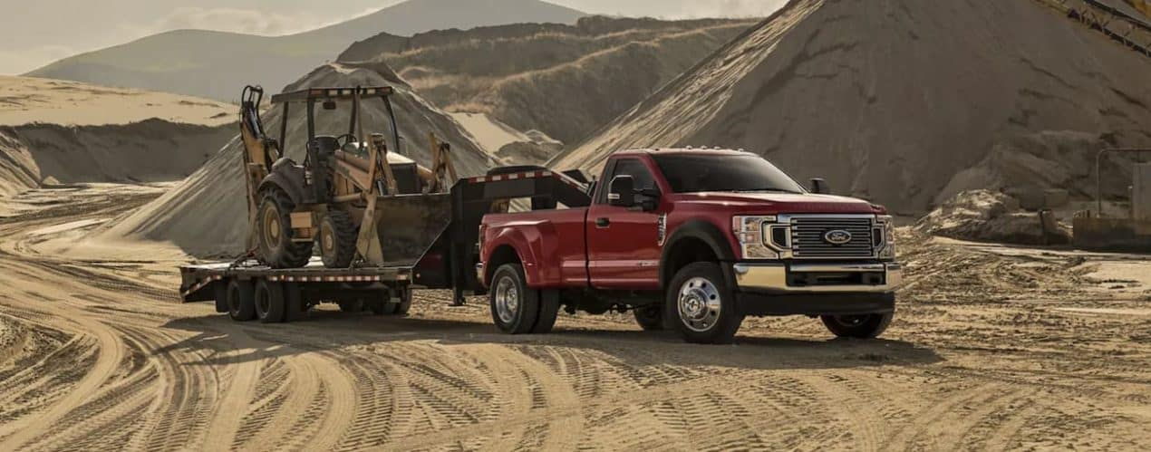 A red 2022 Ford Super Duty is stowing construction equipment at a fill yard.