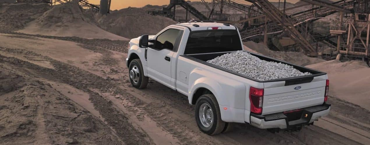 A white 2022 Ford Super Duty is shown driving with a load of crushed stone.