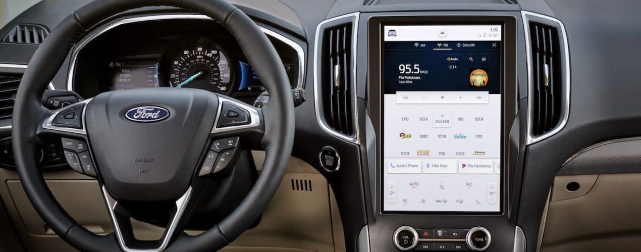 A closeup shows the steering wheel and large infotainment screen in a 2021 Ford Edge.