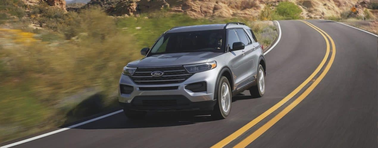 A silver 2021 Ford Explorer is driving on a highway away from rock formations.