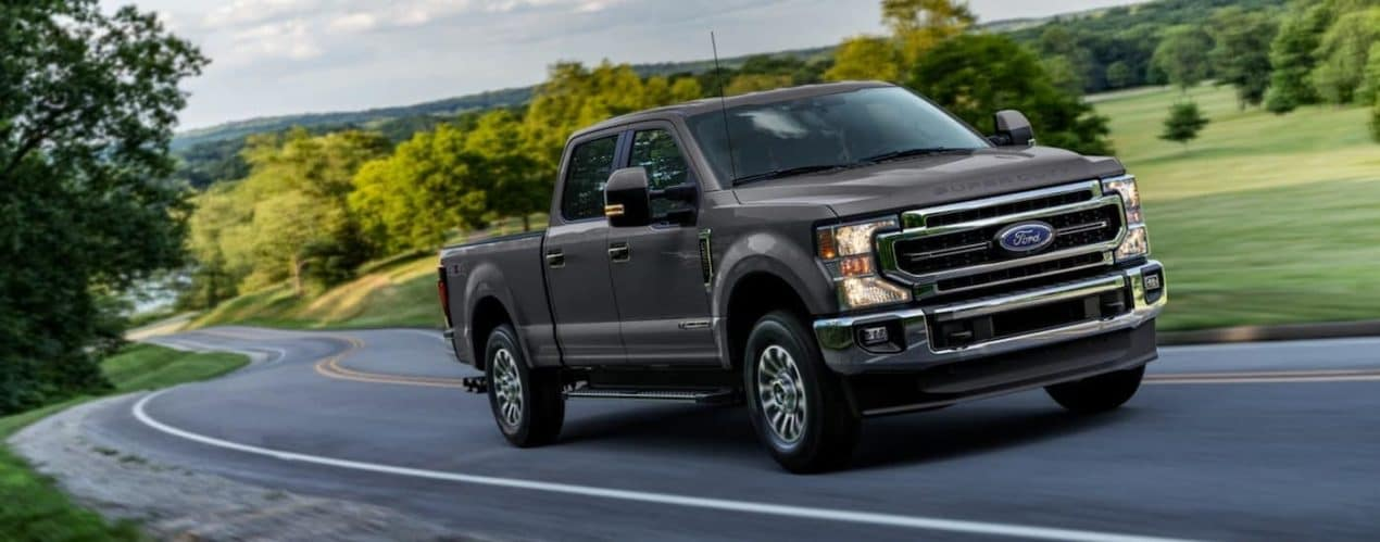 A grey 2021 Ford F-250 Super Duty is driving up a winding road past trees.