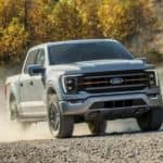 A silver 2021 Ford F-150 Tremor is driving on a dirt trail in the woods.