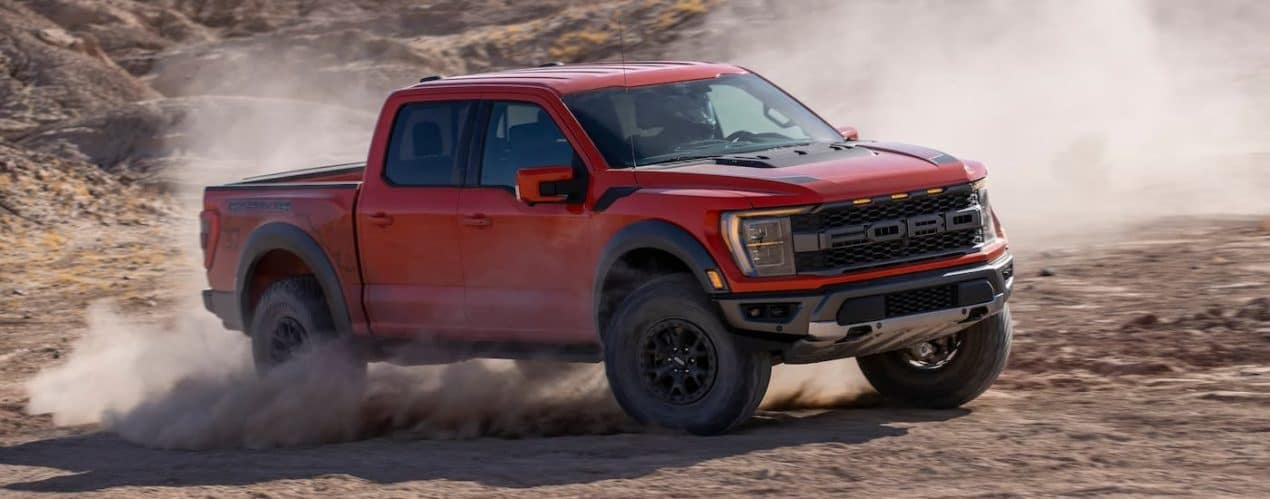 A red 2021 Ford F-150 Raptor is kicking up dirt.
