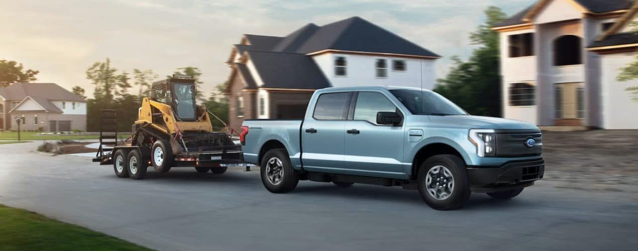 A pale blue 2022 Ford F-150 Lightning Pro is shown from the side towing construction equipment on a suburban street.