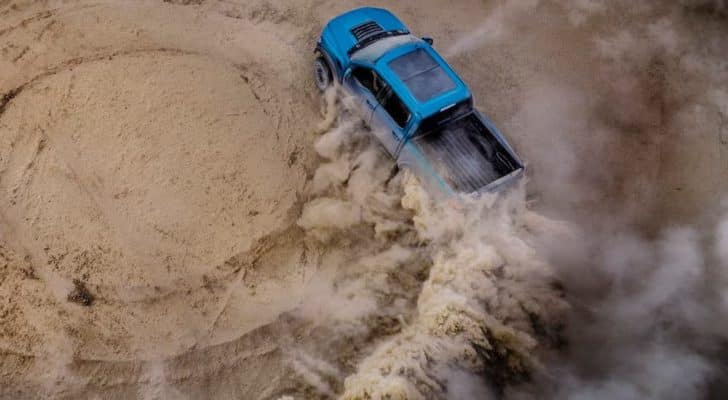 An aerial view shows a blue 2021 Ford F-150 Raptor doing donuts on sand.
