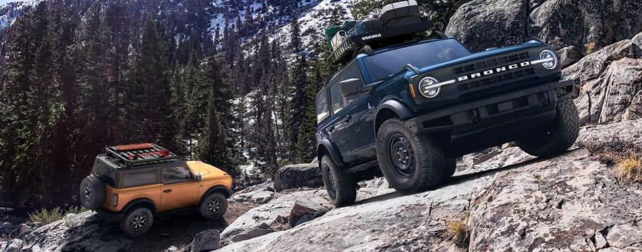 An orange 2021 Ford Bronco 2-door and a blue Bronco 4-door are climbing the side of a rocky mountain.