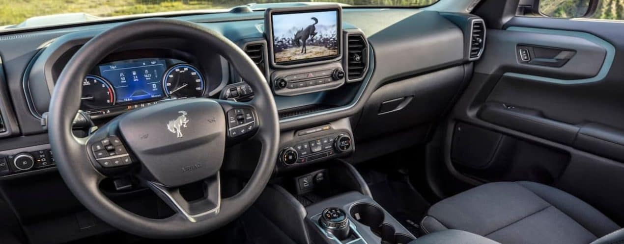 The black interior and infotainment screen is shown in a 2021 Ford Bronco Sport.