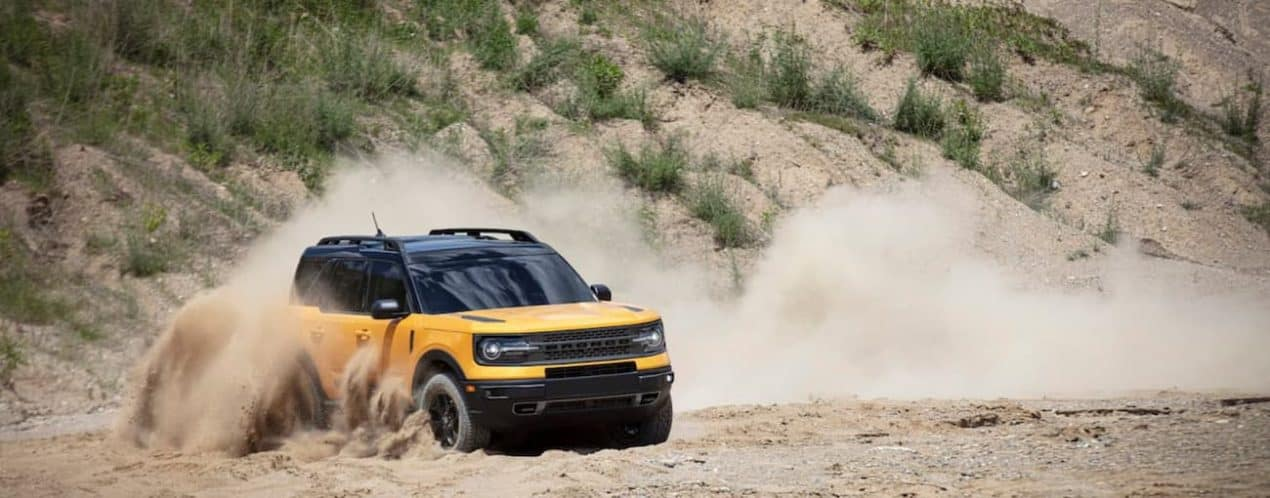 A yellow 2021 Ford Bronco Sport 4-door is shown kicking up sand driving in the dunes.