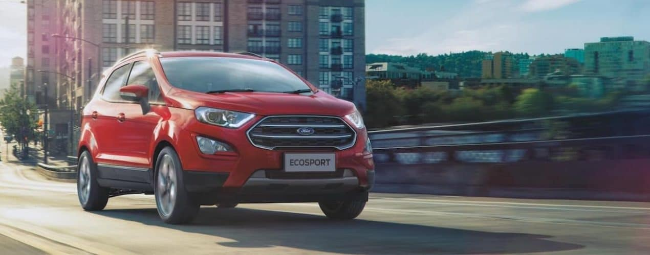 A red 2021 Ford EcoSport is shown driving over a bridge in a city.