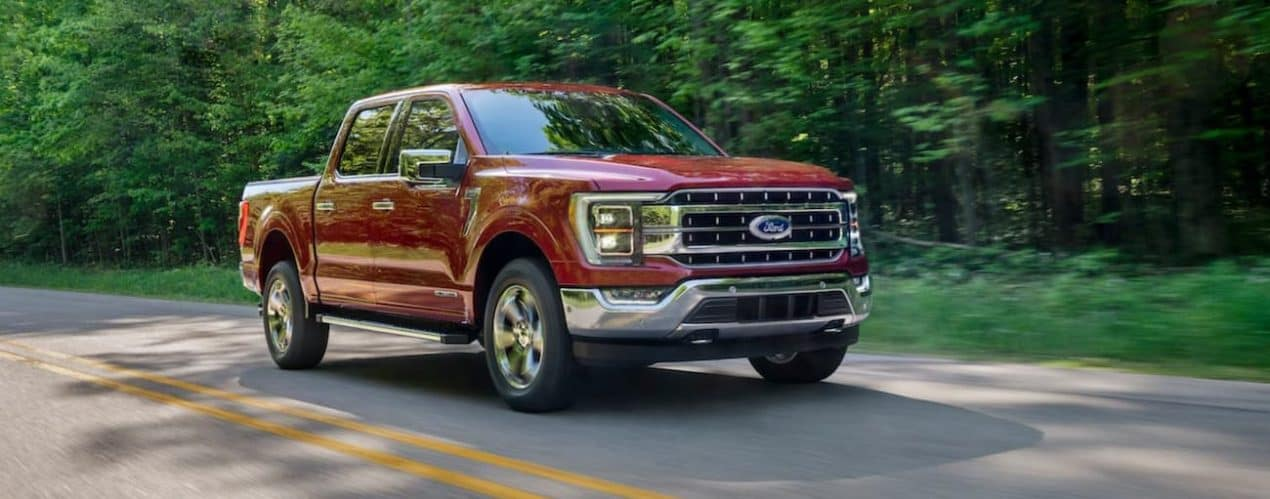 A red 2021 Ford F-150 is driving on a highway past trees.