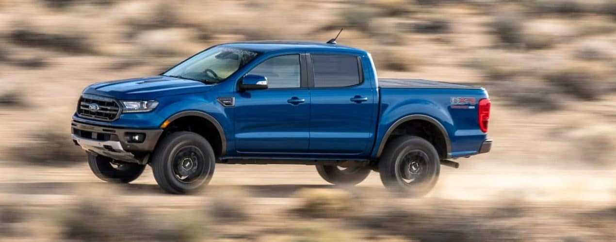 A blue 2021 Ford Ranger is shown from the side driving down a dusty road.